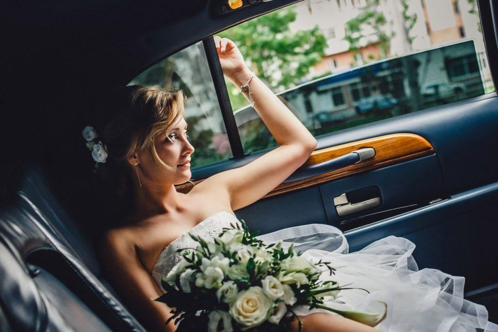 a beautiful blonde bride sitting in a wedding car